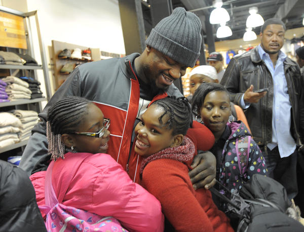 Baltimore Ravens' football player Jameel McClain giving gets hugs from fifth grade students after they received new shoes from him. It was based on their attendance at Matthew Henson Elementary School with the help of DTLR show store and Nike as part of KIcks for KIds program.