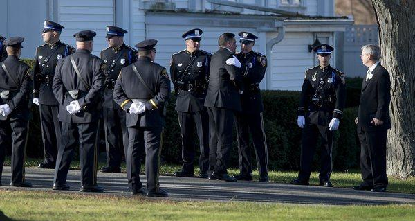 A family member embraces the members of a police color guard before the arrival of the casket at the funeral for Sandy Hook Elementary School teacher Victoria Soto at the Lordship Community Church in Stratford, Conn.