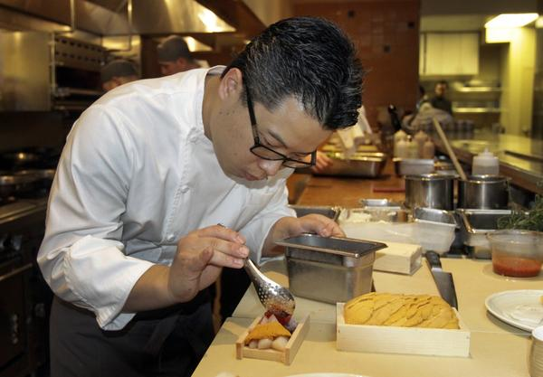 Wolfgang Puck's new chef, Tetsu Yahagi, prepares an Asian-influenced dish in the kitchen.