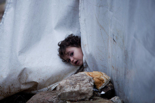 A Syrian girl looks outside her tent at a displacement camp in Azaz, Syria.
