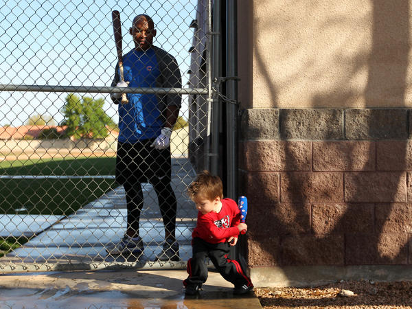 Marlon Byrd watches Reed Johnson's son, Tyce, get ready to take his rips. Cubs pitchers and catchers reported to Fitch Park in Mesa, Ariz., to begin spring training.