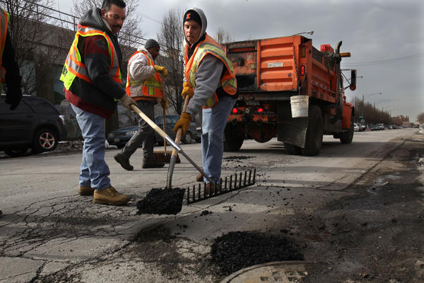 Chicago workers fill pot holes on West Hubbard Street.