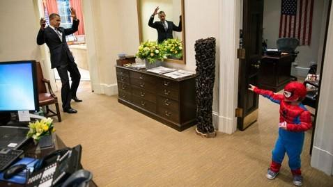 President Obama is ensnared by the webs of a miniature Spiderman visiting the White House.