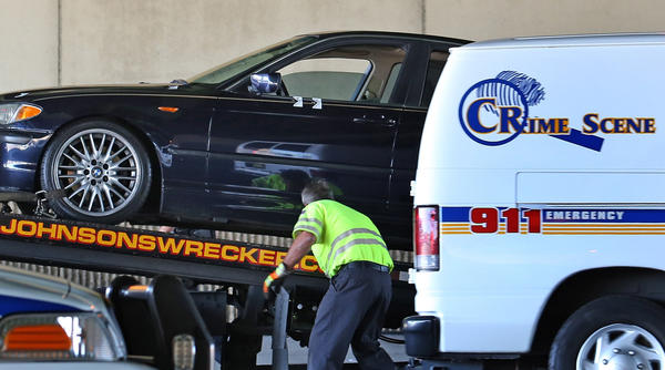 A tow-truck driver loads a vehicle that two bullet holes are marked below the drivers side window.