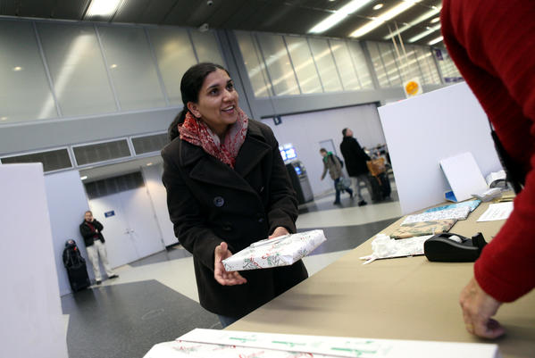 Seema Hooda of Champaign gets a gift wrapped before her flight to Toronto at O'Hare International Airport in 2011. Pam Marino of Chicago volunteered at the airport for their complimentary gift wrapping service.