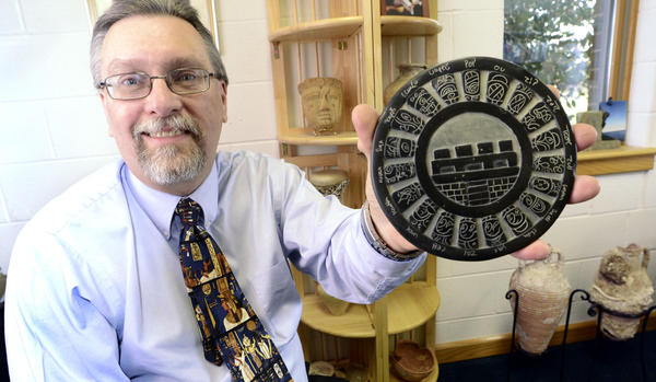 Pastor Franke Zollman of the Seventh-Day Adventist Church in Williamsport holds a reproduction of a Mayan short-count calendar. He said there's no evidence that the end of the current Mayan long-count calendar fortells the end of the world.