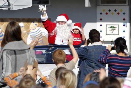 "Santa (retired Costa Mesa Police Helicopter Sgt. Bill Bechtel) waves to the crowd as he arrives to rousing cheer with student James Sick, during his visit to Woodland Elementary School to hand out candy canes to the 525 kids in on the school's playground. Sick won the chance in an auction to be Santa's helper during the school's ""Fall Flingo"" fundraising event to benefit the Kaiser-Woodland School's Foundation science program."