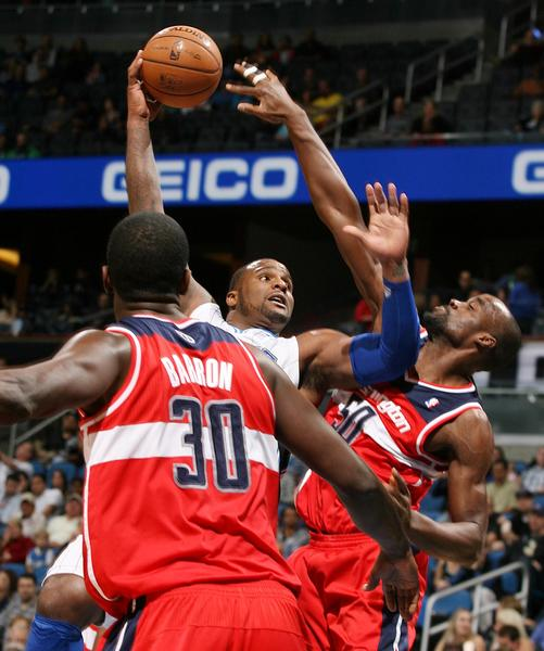 Orlando Magic forward Glen Davis, middle, shoots between Washington Wizards forward Earl Barron (30) and center Emeka Okafor (50) during an NBA game at the Amway Center on Wednesday, December 19, 2012, in Orlando, Florida.