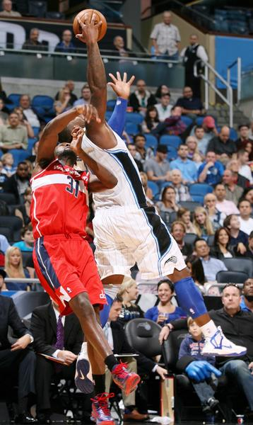 Orlando forward Glen Davis (right) leaps high to reach a pass over Washington forward Chris Singleton (31) during the Washington Wizards at Orlando Magic NBA game at the Amway Center on Wednesday, December 19, 2012. Orlando won the game 90-83.