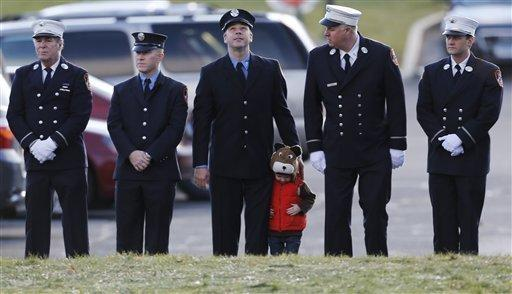 A child lines up with firefighters outside the funeral for Newtown, Conn., school shooting victim Daniel Gerard Barden, who wanted to be a firefighter when he grew up.