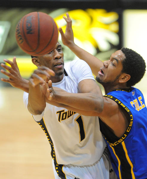 Coppin State's Patrick Cole closely guards Towson's Marcus Damas at midcourt in the first half.