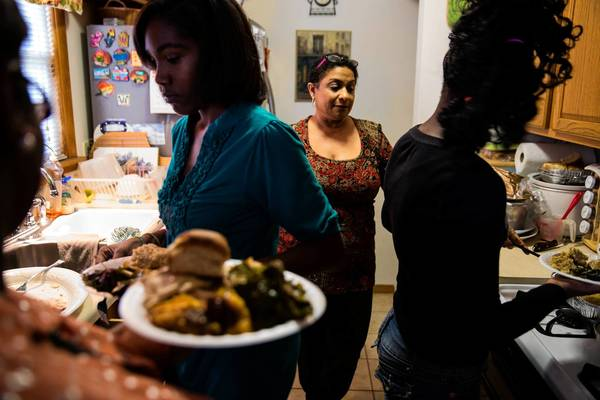 Pamela Carthan, center, watches as her adopted daughter Ali, 15, left, and foster child Naja, 12, dish up Thanksgiving dinner at their home in Chicago Heights. Carthan, 53, is also foster mother to Krystal, a 17-year-old.