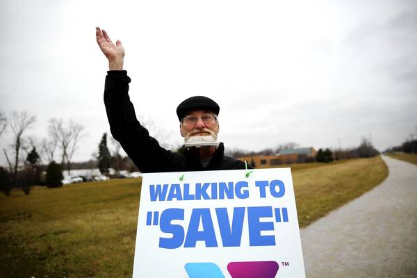 Steve Joelson, left, talks with lifelong friend David Hall, a former Lake County judge, as they walk with other YMCA supporters Dec. 7 in Waukegan. Hall, who has Lou Gehrig's disease, plans to walk 100 miles this month.