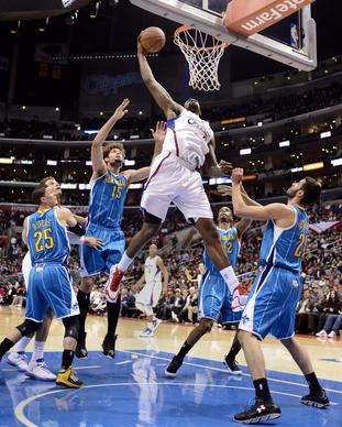 DeAndre Jordan dunks as New Orleans Hornets look on during first half.