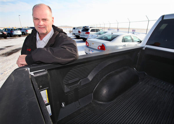 Scott Meier, owner of Avis Rent A Car in Aberdeen, leans on one of the pickups in his fleet of rental vehicles. Meier said trucks and SUVs are popular rental requests for hunters since they offer more room for gear and dogs.