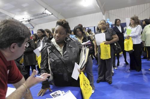 Daniel Ojeda, the recruitment manager for the Illinois Department of Human Services, instructs Dolton resident Qiana Mosely on applying for a job during the Thornton Township Community Job Fair at South Suburban College in South Holland, Ill. on Wednesday. Mosely was among around 2,000 people vying for jobs with 50 employers.
