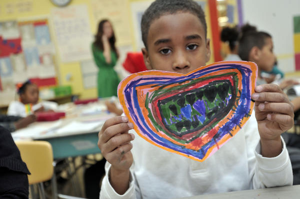 "Braydon Smith, 6, holds up a paper heart he made so people in Newtown, Ct. will smile. Smith wrote the word ""Love"" twice on it and included several hearts. Students in Caitlin Houston's first grade class in Dallas F. Nicholas Sr. Elementary School make hearts for ""Paper Hearts Across America,"" an initiative launched in Montana to link millions of paper hearts to Newtown, Ct."