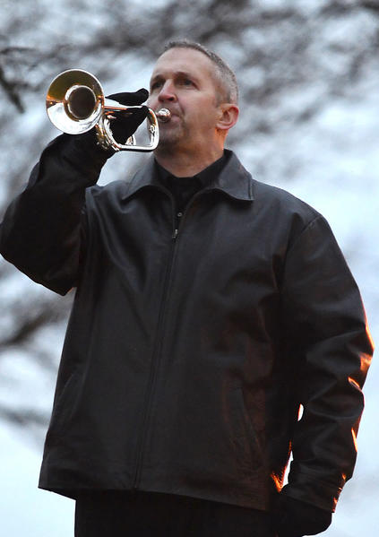 Todd Kirkwood, of Greencastle, Pa., plays taps Wednesday at the flag pole in front of Greencastle-Antrim Elementary School. The  playing of taps was a tribute to the lives lost in the shooting at Sandy Hook Elementary School in Connecticut. Taps is being played each day this week at 5 p.m. at Greencastle-Antrim Elementary School. Kirkwood is a member of Buglers Across America.