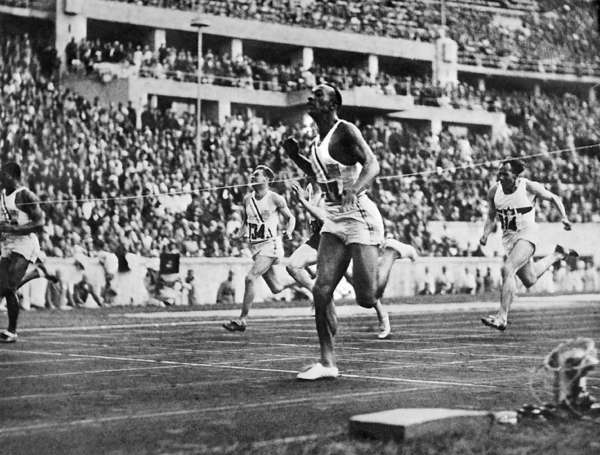Jesse Owens crosses the finish line to win the 100-meter dash at the 1936 Olympics.