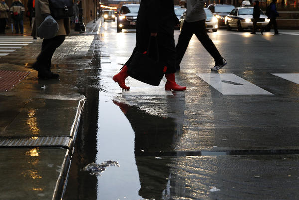 Commuters dodge puddles at South Wacker Drive at West Madison Street in downtown Chicago today.