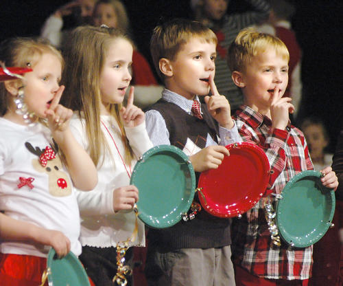 Charlevoix Elementary School students (from left), Evie Tuck, Kylee Rice, Joshua Schultz, and Hudson Vollmer do actions with a song as they and their classmates perform during the school's kindergarten and first grade Christmas sing-along at the Charlevoix High School auditorium Wednesday.