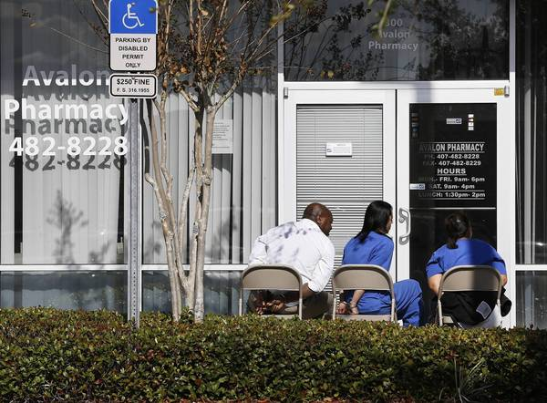 Valentine Okonkwo, left, sits outside of his pharmacy in handcuffs on November 29, 2012. Authorities are searching the Avalon Pharmacy, located in a shopping center on South Avalon Park Boulevard in Orlando. (Jacob Langston/Orlando Sentinel)