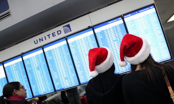 Travelers check flights at O'Hare International Airport in December 2011.
