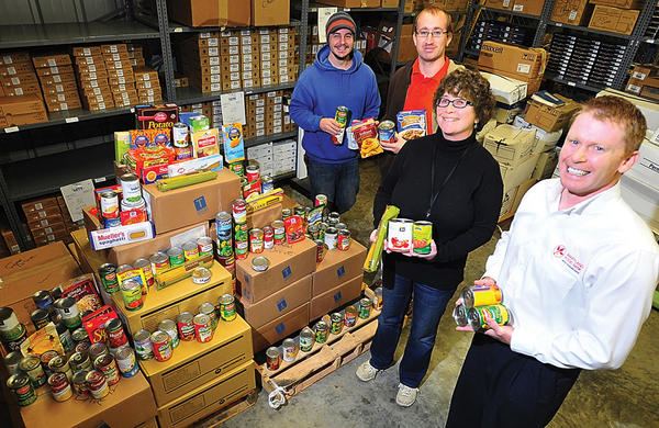 Antietam Cable employees, from left, Ryan Smith, Donald Stone and Cindy Garland present collected food items Nov. 15 to Maryland Food Bank Western Branch Executive Director Matt Thompson.
