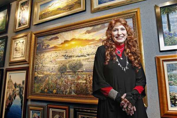 "Artist Ruth Mayer poses for a portrait in front of her painting titled ""Jerusalem"" at her gallery in Laguna Beach on Dec. 14."