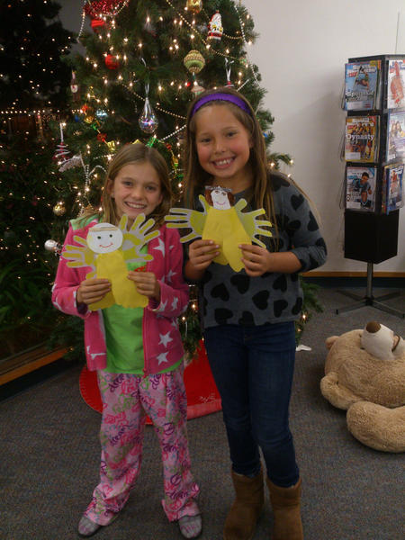 Lucy and Maggie hold angels they made at the Friends of the Library sponsored Family Winter Night on Wednesday at the Laguna Beach Public Library. All the angels will be sent to Newtown, Conn., with the name of the child who made it and a special text.