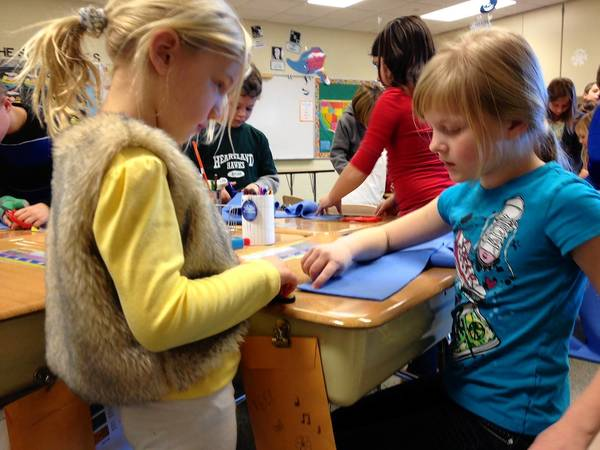 Geneva students Samantha Ayars, 9, and Chloe Koster, 5, work together to make a scarf that will be donated to Marianjoy Rehabilitation Hospital.