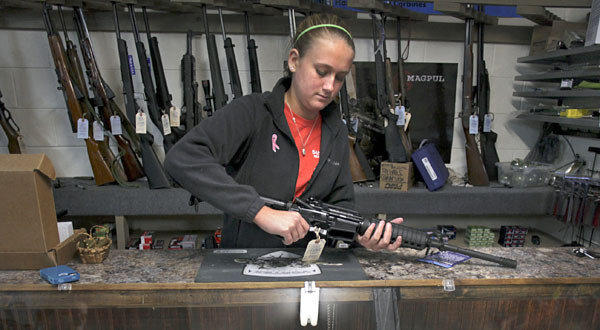 Atlas Tactical co-owner/operator Brooke Stallings handles an assault rifle that is for sale in her shop near Newport, Va.