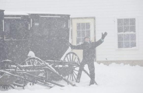 An Amish boy plays in snow outside a one-room schoolhouse in Kingston, Wis.