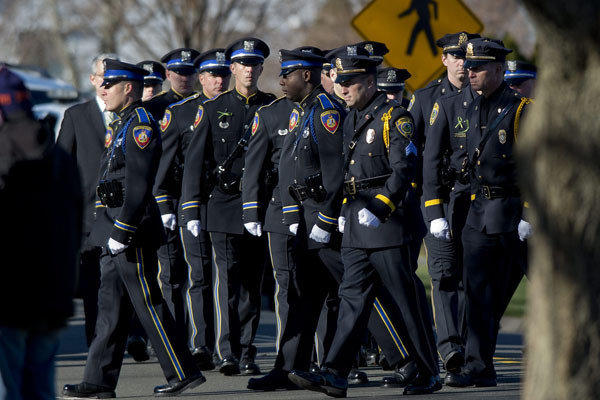 A police color guard attends the funeral for Sandy Hook Elementary School teacher Victoria Soto. The Milwaukee County Sheriff has advocated putting an armed officer in every school.