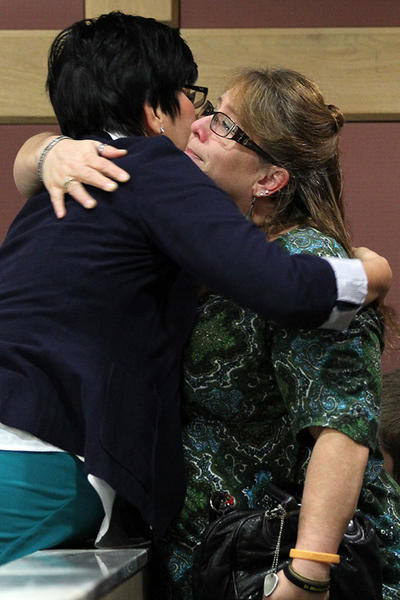 Michael Brewer's mother, Valerie Brewer, right, hugs Assistant State Attorney Maria Schneider following a sentencing hearing for Matthew Bent at the Broward County Courthouse in Ft. Lauderdale on Thursday, Dec. 20, 2012. Matthew Bent was sentenced to 11 years for his conviction on a charge of aggravated battery in the burning of Michael Brewer.