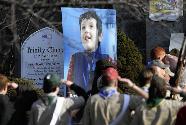 Boy Scouts salute as a funeral procession for Benjamin Wheeler, 6, enters the Trinity Episcopal Church in Newtown, Connecticut. Benjamin, a member of Tiger Scout Den 6, was killed when 20 children and six adults were massacred at Sandy Hook Elementary School last Friday