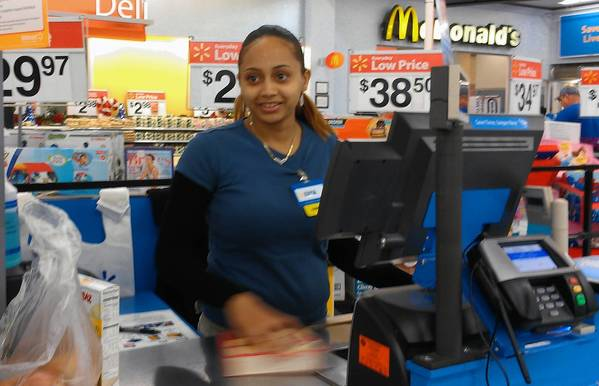 Kayla Rackard, a seasonal cashier at Walmart in Casselberry, checks out a customer at the store on Tuesday, Dec. 18, 2012. (Sara K. Clarke, Orlando Sentinel)