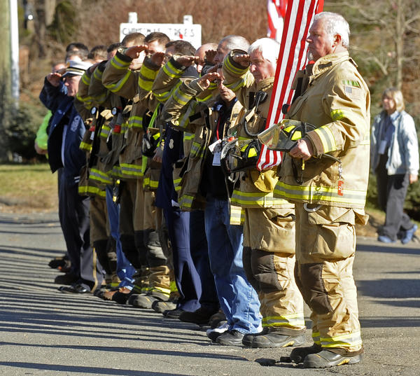 Sandy Hook volunteer fire fighters salute a funeral procession on Riverside Road near Sandy Hook Elementary School Thursday. More funerals took place for some of the 26 victims of Friday's shooting.