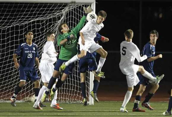 Laguna Beach High's Reed Matthews (5) boots the ball into the net as teammate Harrison Gregory leaps into the mix to get the ball past the Trabuco Hills' goalie.