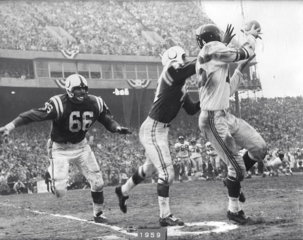 Colts' Andy Nelson leaps up for the interception, grabbing the ball from the Giants' Frank Gifford in the 1959 NFL Championship game.