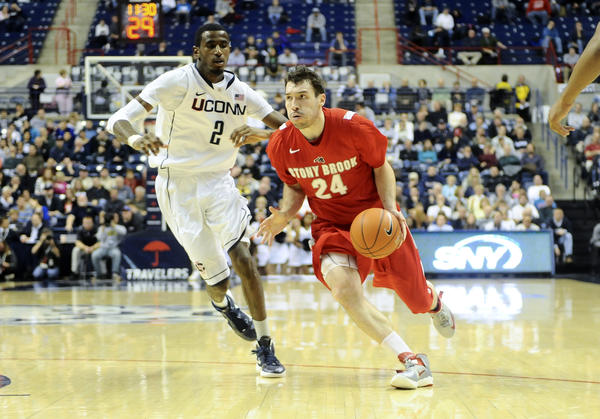 Stony Brook forward Tommy Brenton dribbles against UConn.