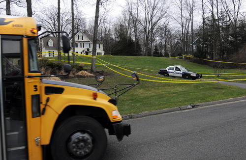 A school bus drives past the home of Nancy Lanza at 36 Yogananda St. in Sandy Hook, the mother of Adam Lanza, who also lived there. The house is surrounded by police crime tape and has a police presence in the driveway and the street. State police detectives have been combing the 4,000 square-foot house since moments after the gunfire stopped inside the school trying to find clues as to why Adam Lanza shot his mother and then went on to kill 26 others.