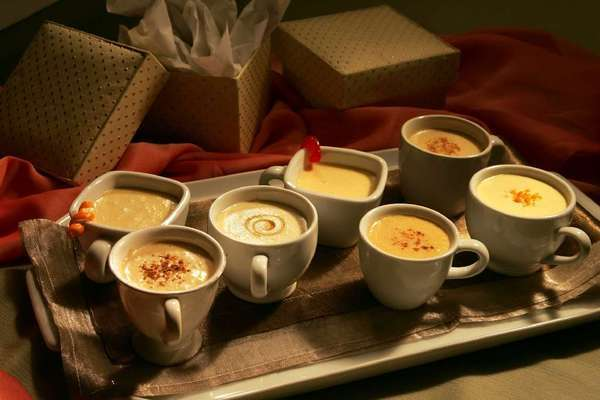 Flavored eggnog variations, from left: tequila-orange nog (with orange twist), rum nog with coconut milk, scotch-honey nog (with chestnut honey swirl), gin-maraschino nog (with cherry), nut brittle nog with hazelnut liqueur, rye whiskey-vanilla nog and amaretto-apricot nog (with grated orange zest).