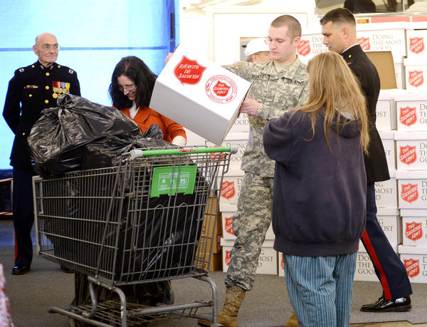 Marine PVC Brandon Moats loads food in carts at the annual Salvation Army/Toys for Tots giveaway program on Thursday.