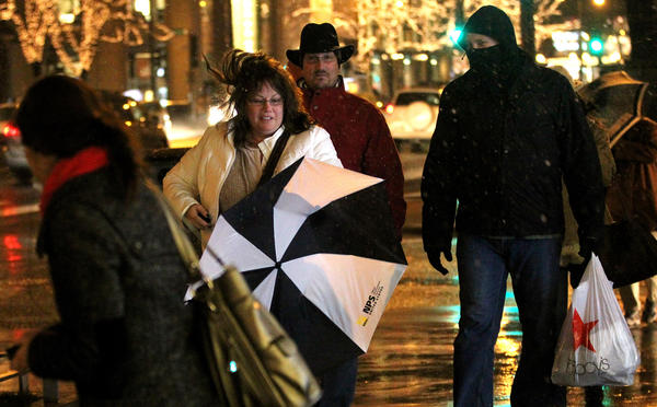 A woman loses control of her umbrella while walking on North Michigan Avenue in Chicago as strong winds blow and a mix of rain and snow falls.