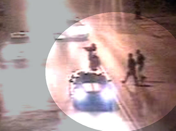 "This is one of two surveillance images Baltimore police released of a group of ""persons of interest"" walking across Greenmount Avenue on the night of a triple shooting there."