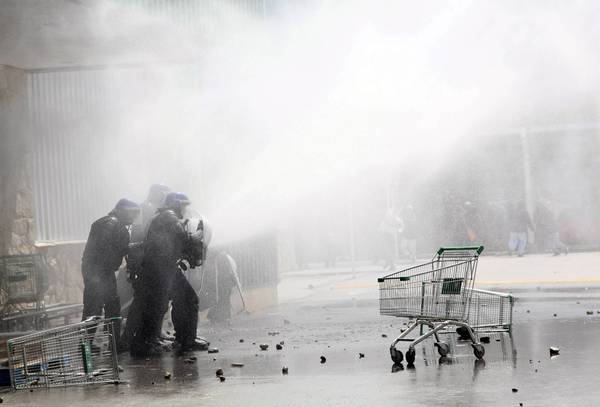 Anti-riot policemen fire tear gas to looters in the Argentine Patagonian city of San Carlos de Bariloche December 20, 2012. Crowds of people broke into several supermarkets in the ski resort town of San Carlos de Bariloche resulting in rioting and looting, according to local media. Looters stoned the police who responded with tear gas. Almost all the stores in the area have been closed for the rest of the day. Cabinet Chief Juan Manuel Abal Medina announced that four hundred gendarmes will be send to maintain security around the area.