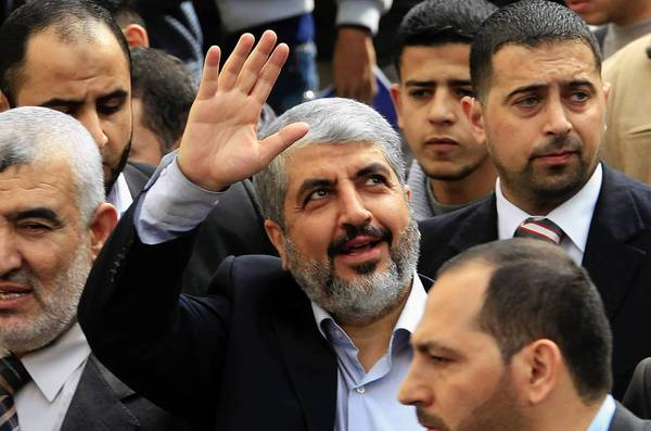 Exiled Hamas leader Khaled Meshaal waves to Palestinian students during his visit to the Islamic University in Gaza City on Dec. 9