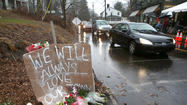 Cars glide by the memorial in Newtown just before the moment of silence Friday morning in Newtown, Conn.
