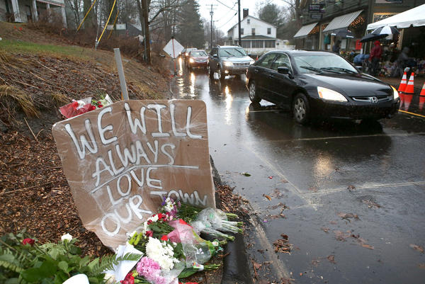 Cars glide by the memorial in Newtown, Conn., before the moment of silence Friday morning.